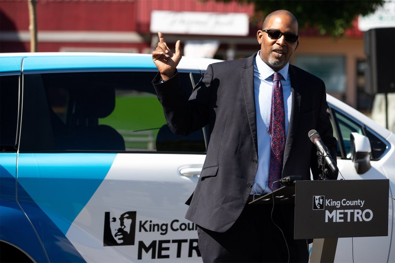 Photo of De'Sean Quinn speaking at a podium with King County Metro's logo on it in front of a Via to Transit vehicle.