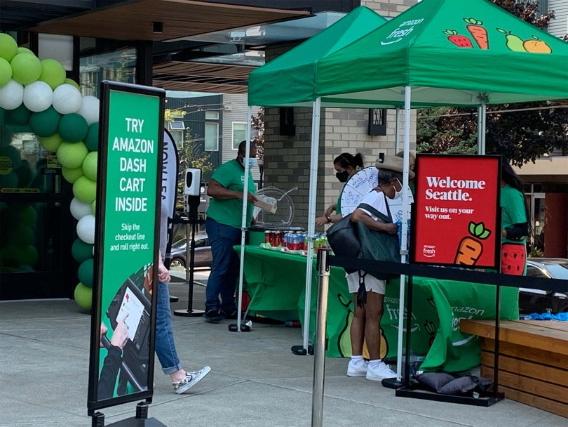 """Booths at the entrance of the Amazon Fresh Jackson store on opening day with green signs advertising Amazon's Dash Cart and a red sign with white text that reads """"Welcome Seattle. Visit us on your way out."""""""