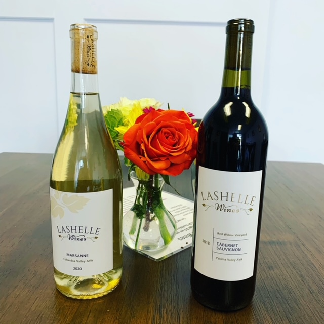 Photo depicting two bottles of wine, the left a bottle of Marsanne (white wine) and the right a bottle of Cabernet Sauvignon (red). In between the two bottles sits a vase with two roses, one red and one yellow.