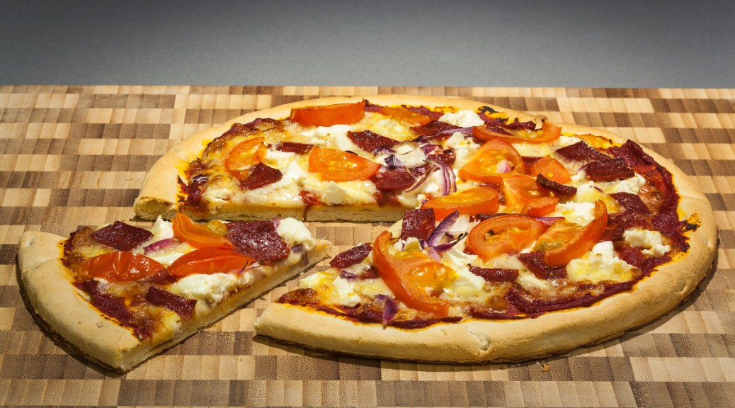 Photo of a pizza topped with tomatoes, pepperoni, and red onions on a background of a wooden checkerboard.