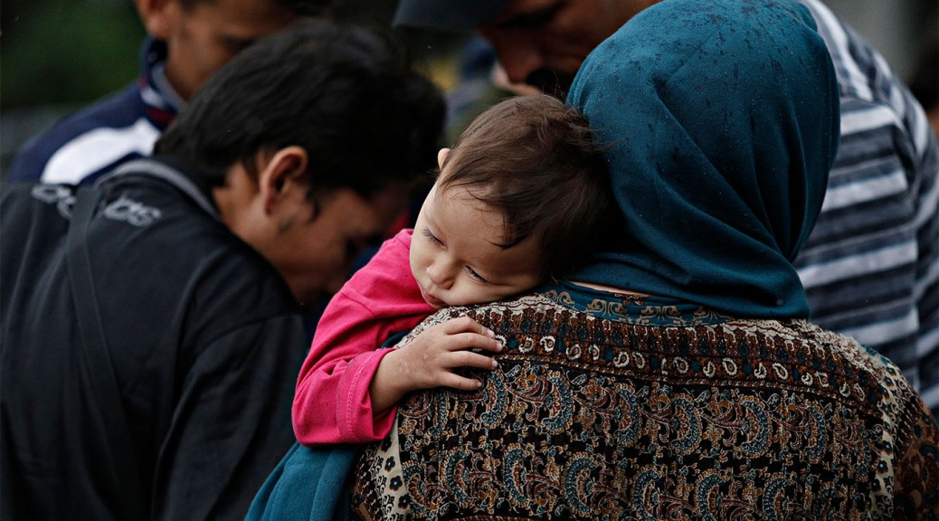 Photo depicting a family of refugees resting in a square. A youth with a pink shirt rests their head on the shoulder of a female-presenting refugee whose head is wrapped in a blue headscarf.