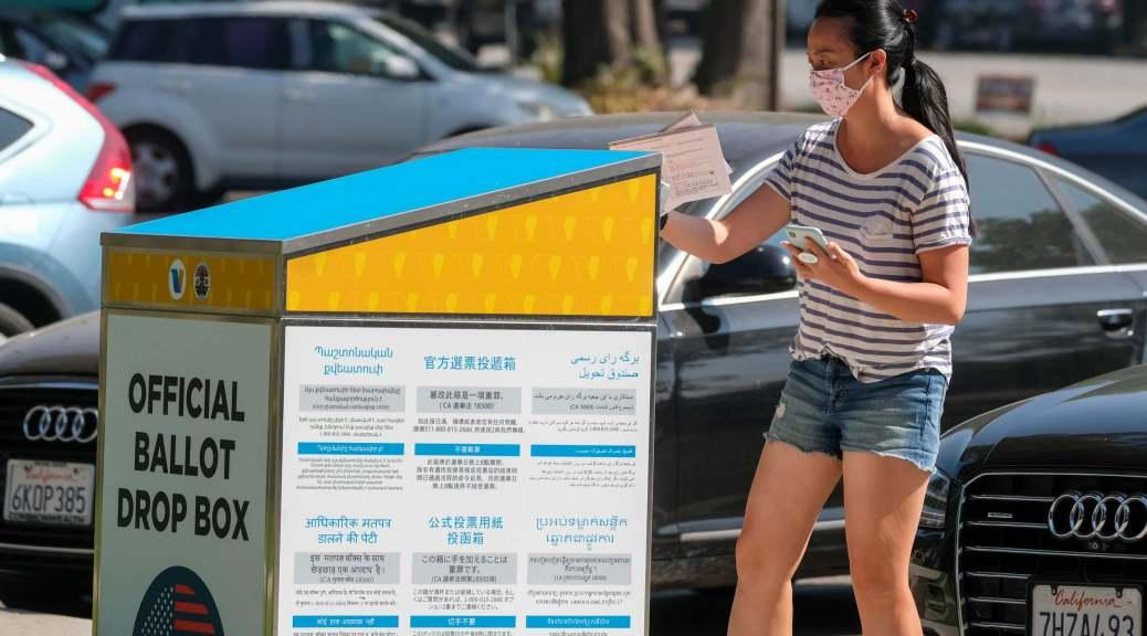 A woman wearing a face mask drops her ballot into an official ballot drop box.