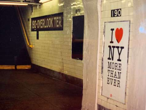 """Photo depicting an empty 190th subway platform in New York with a sign that says """"I (heart) NY more than ever."""""""