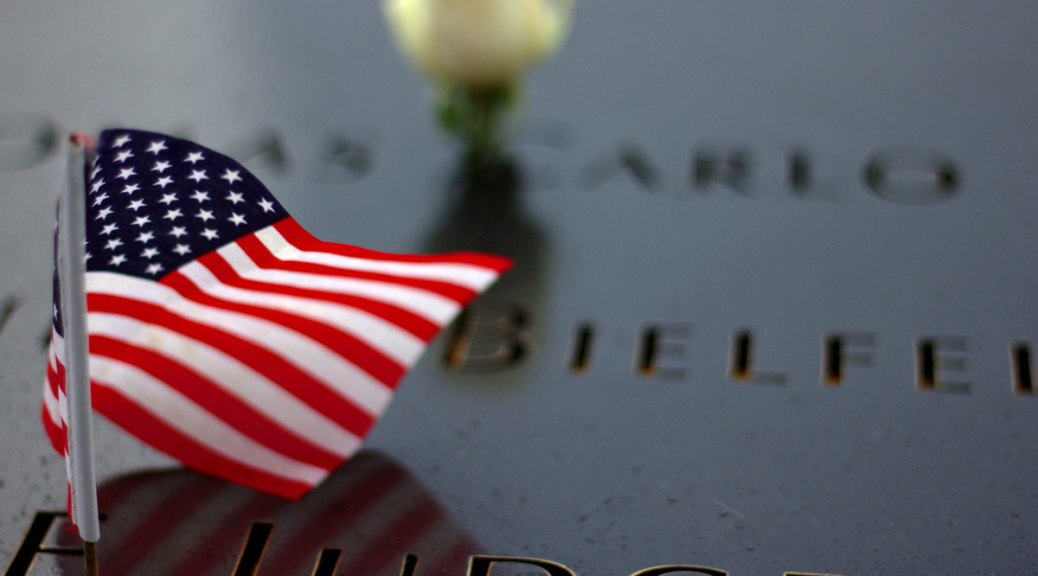 A small U.S. flag on a 9/11 memorial engraved with names of those lost in the terrorist attack. A blurred yellow rose is in the background.