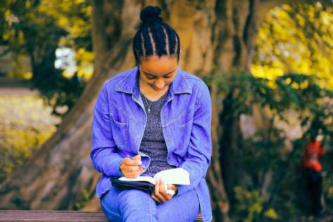 Photo depicting a Black- and female-presenting individual sitting on a bench in front of a tree writing in a notebook.