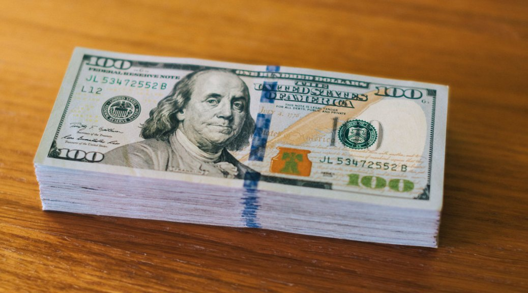 A stack of $100 bills. Image attributed to Ervins Straumanis under a Creative Commons 2.0 license.