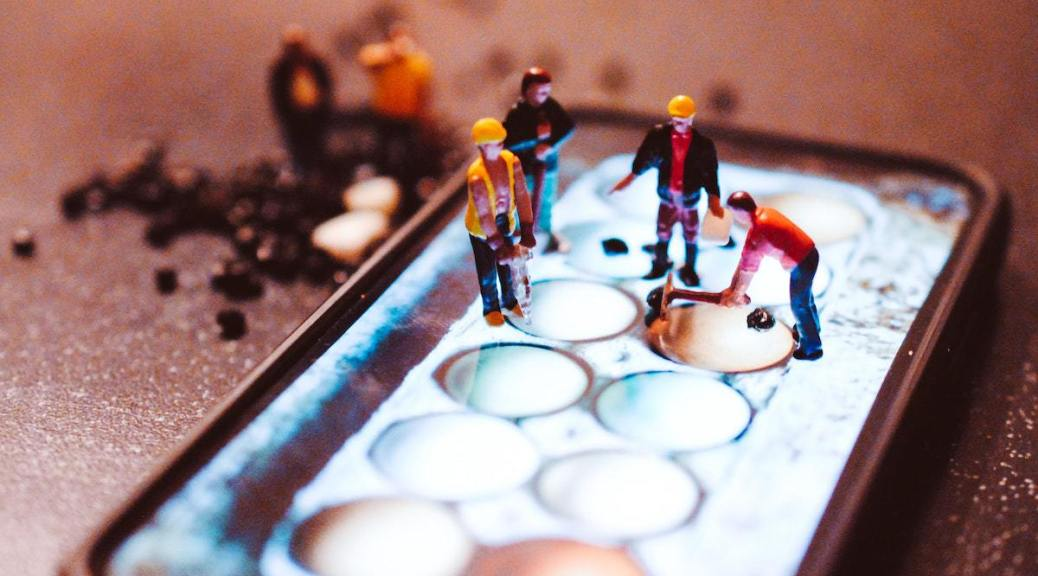 Photo depicting miniature figurines of construction workers working on a cellular phone.