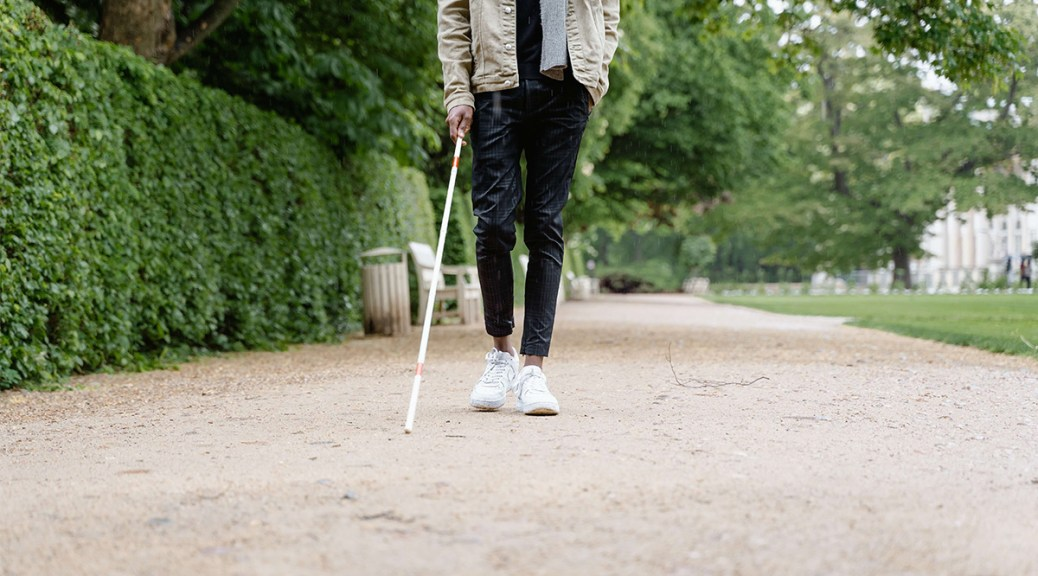 Photo depicting a male-presenting individual holding a walking stick for the blind. Only the individual's white tennis shoes, jeans, and hand holding the walking stick are shown. A park adorns the background of the photo..