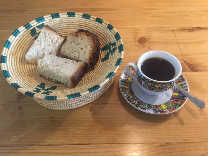 Photo depicting a cup of Ethiopian coffee on a saucer, decorated with color images of people and buildings, and sweet bread in an intricately woven basket with a teal-blue pattern.