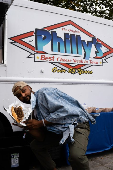 Photo depicting a man posing with a Philadelphia cheesesteak sandwich in front of the white The Original Philly's food truck.
