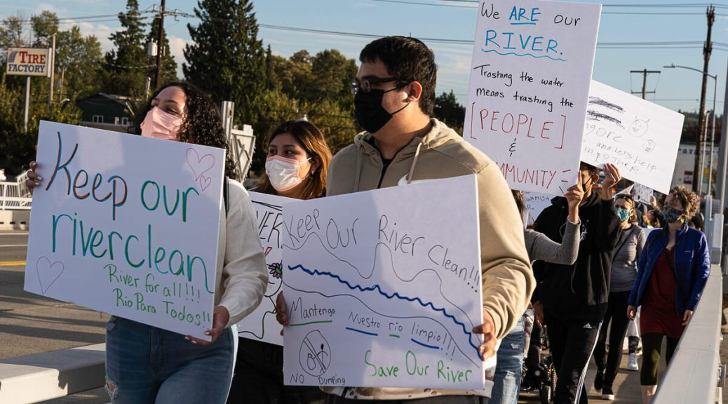 """Photo depicting community members marching across a bridge holding various signs that have slogans like """"Keep our river clean"""" written on them."""