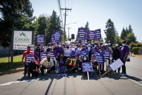 """Health care workers stand and sit posing for a picture holding purple and white protest signs that say things like, """"Safe Staffing Saves Lives"""""""