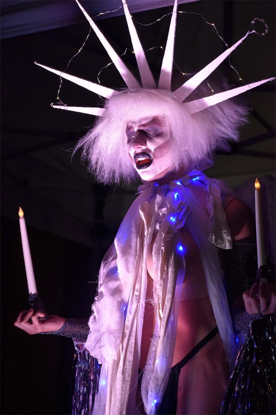 Photo depicting Angel Baby Kill Kill Kill performing with two battery-operated candles.
