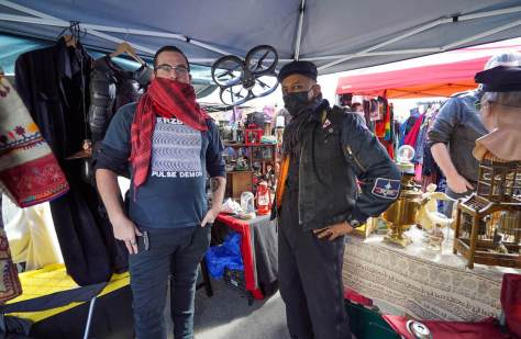 Photo depicting two male-presenting individuals posing inside a vintage ware booth at an outdoor flea market.