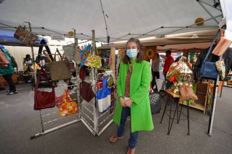Photo depicting Molly McCoy in a bright-green coat standing next to the purses she sells inside a flea market booth.