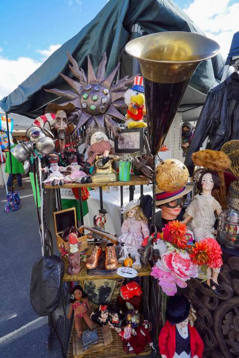 Photo depicting various antique and vintage wares at a flea market booth.