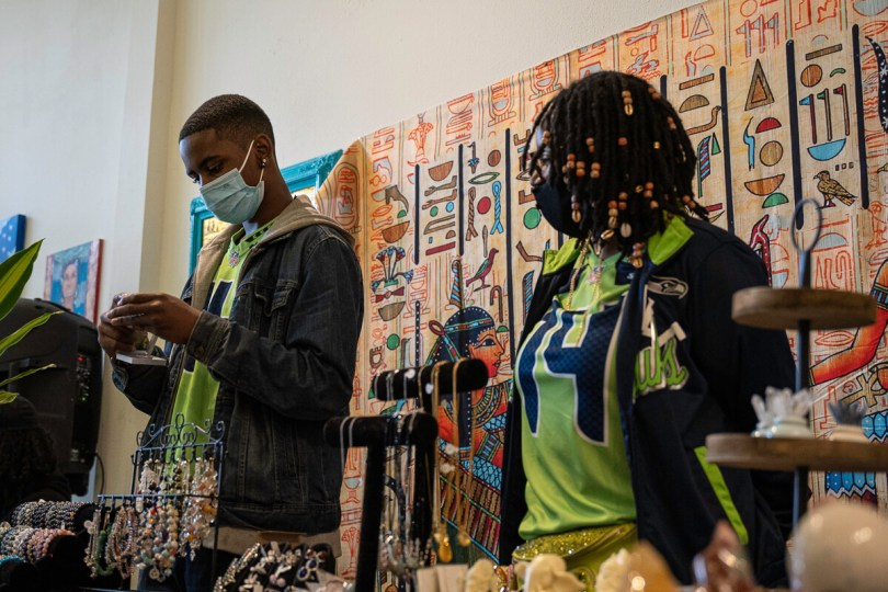 Photo depicting two Black-presenting individuals looking at crystals and jewelry from Nefertiti Holistic's booth at The Liink Project.
