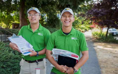 Photo depicting two male-presenting individuals in green Waste Management polo shirts and baseball caps smiling and carrying clipboards full of recycling and reducing waste papers on a residential sidewalk.