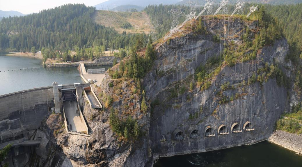 Photo depicting a hydroelectric dam during the day surrounded by mountains with trees.