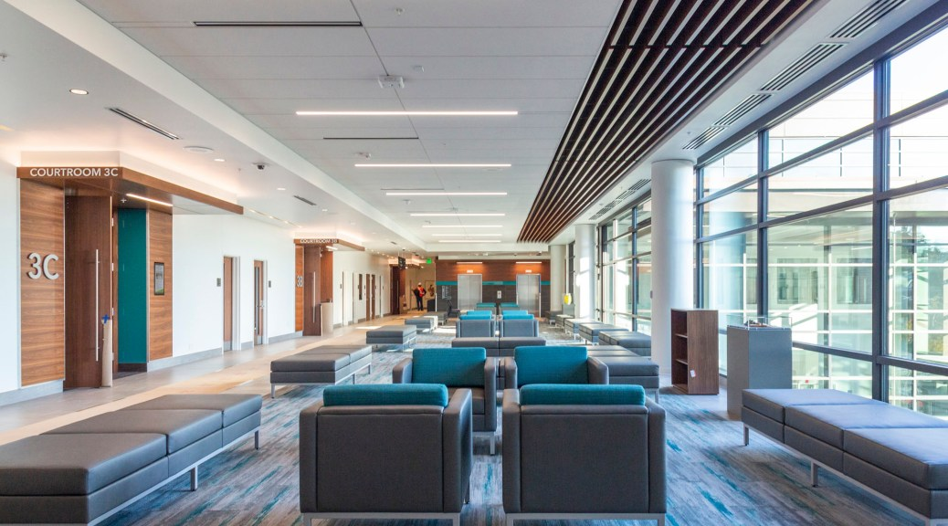 Photo depicting the interior of the King County Family Justice Center with blue-and-grey-striped rug and what feels like endless blue and grey chairs for seating.