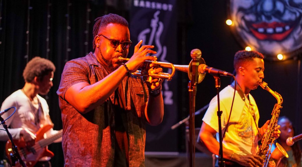 Photo depicting Marquis Hill Blacktet playing a trumpet into a microphone on stage. His backup musicians play a guitar and saxophone in the background.