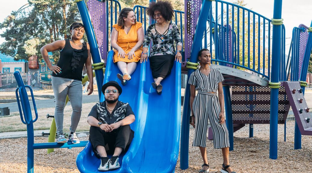 Photo depicting the Lavender Rights Project members posing against a blue-and-purple playground jungle gym and slide.