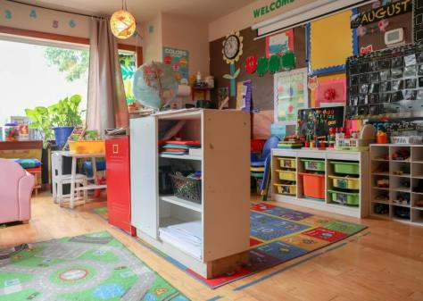Interior of a pre-school classroom in primary colors with colorful rugs, bins, cabinets, and toys.