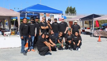 Photo depicting members and volunteers of SPMA wearing black t-shirts posing in front of numerous pop-up tents at one of their weekend markets.