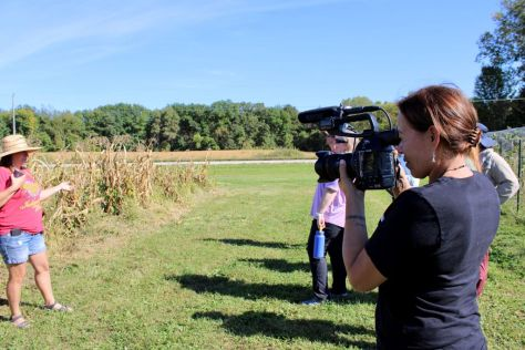 Photo depicting Katsitsionni Fox filming an individual standing in a field.