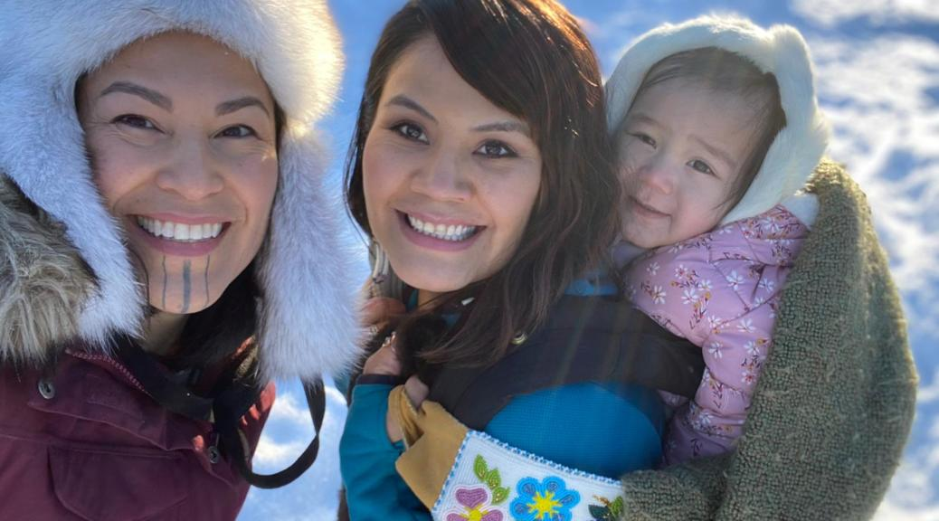 Photo depicting two female-presenting Indigenous individuals smiling up into the camera. One of the individuals carries a youth on their back.