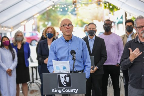 """Photo depicting Dr. Jeffrey Duchin speaking at a press conference at a podium that reads """"King County."""""""