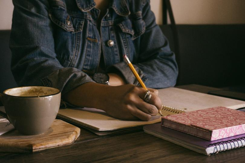 Photo depicting a woman writing on a spiral-bound notebook in a well-lit room. A grey cup of coffee sits beside her hand and another two notebooks sit in front of the one she's writing in.