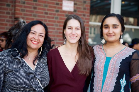 Photo depicting three female-presenting individuals smiling into the camera.