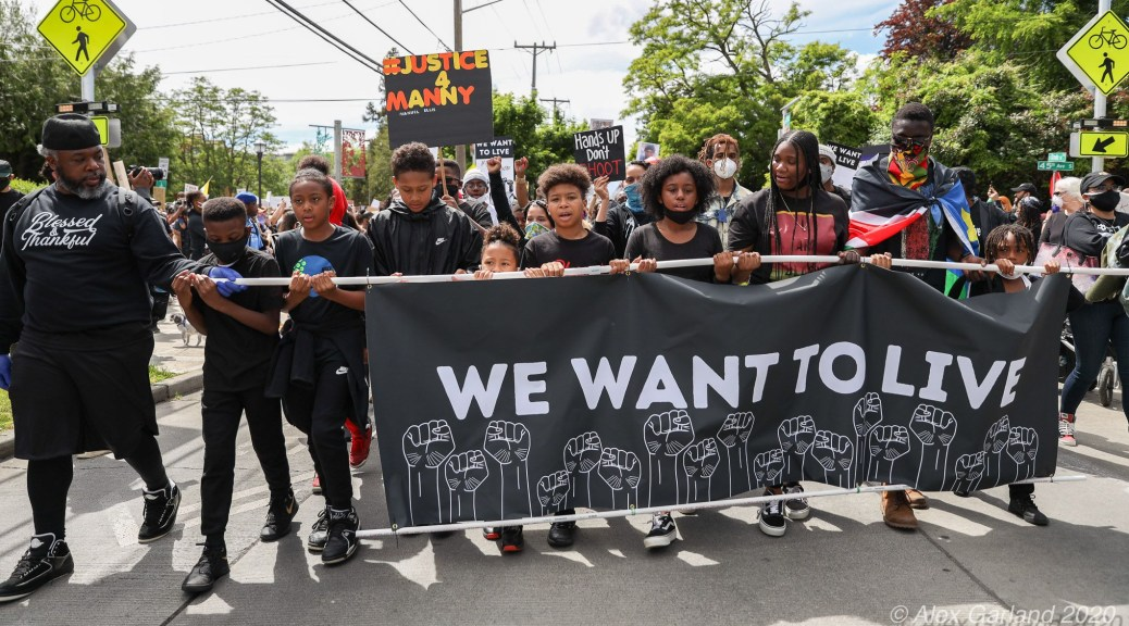 """Black youth protestors carry black banner with white raised fists and text that reads """"We Want To Live."""""""