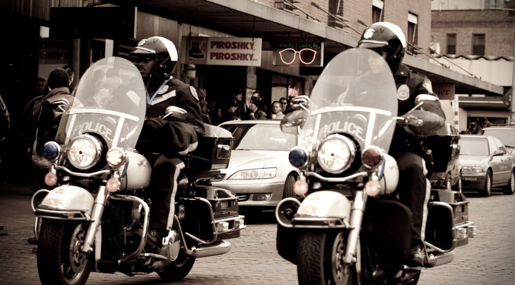 Sepia-toned photo depicting two police officers on motorbikes escorting down a street through Pike Place Market in Seattle.