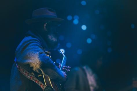 Photo depicting a bearded guitar player within a dark blue room