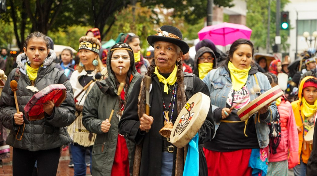 Photo depicting Indigenous individuals walking as a group while playing traditional drums to celebrate Indigenous Peoples' Day.