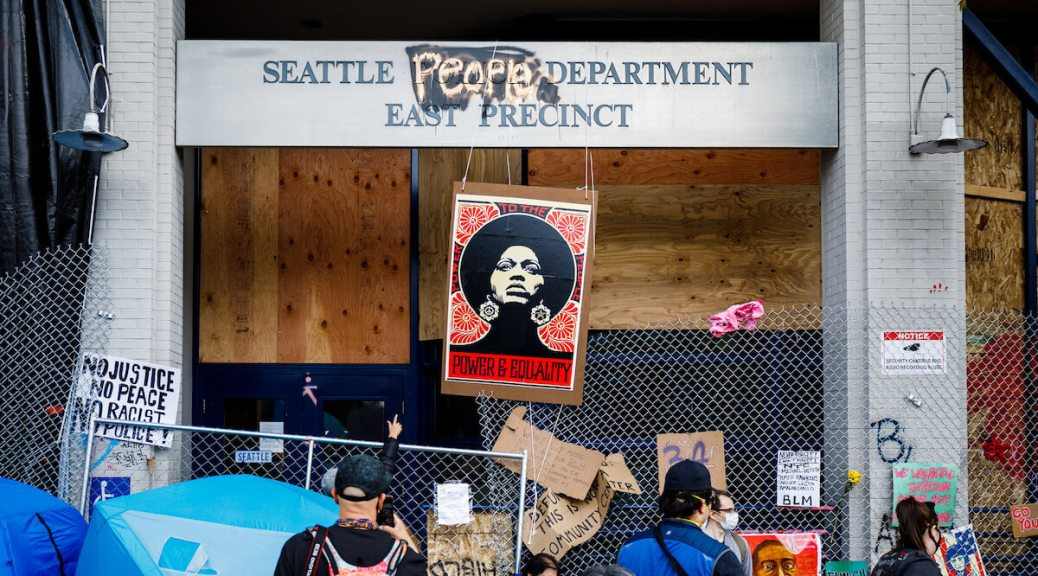 """SPD East Precinct post-evacuation, with sign changed to read """"Seattle People Department."""" A poster of Angela Davis hangs in the center of the blocked entrance."""