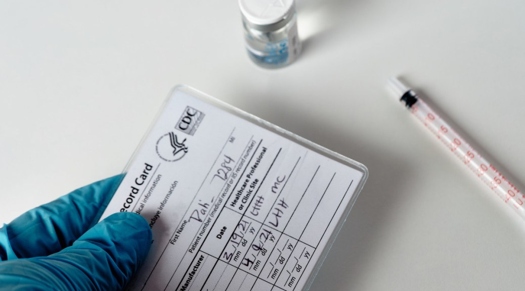Photo depicting a blue gloved hand holding a U.S. COVID-19 vaccination card. In the background sit a vial of vaccine and a syringe.