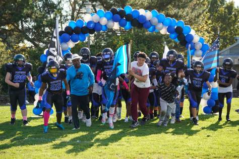 Photo depicting the CD Panthers 13U team running under a blue, black, and white balloon arch to the football team to start their game.