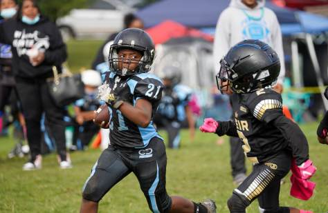 Photo depicting Jamari in CD Panthers' blue and black football uniform running for a touchdown past a Heir player in black and gold.