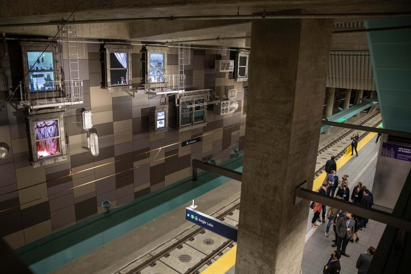 """Photo depicting the interior of the new U District Station platform with the artwork """"Fragment Brooklyn"""" hanging on a wall opposite the platform."""