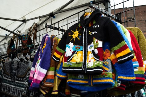 A display of child garments at the Sumac El Sol Handcrafted Textile Arts vendor stall.