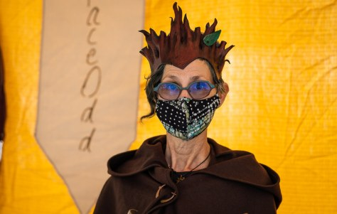 Photo depicting Tamara Clammer wearing a handmade face mask against a yellow backdrop.