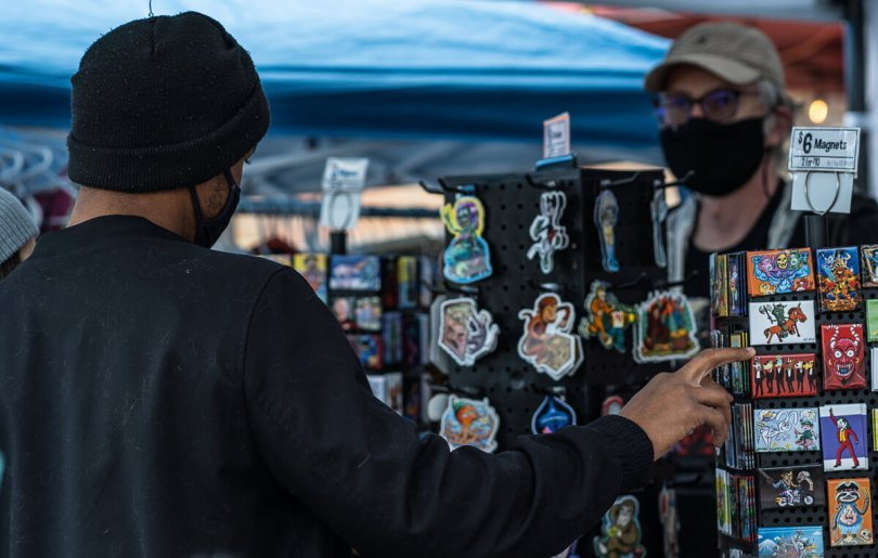 A customer browses through custom magnets sold by Eli Wolff (right).