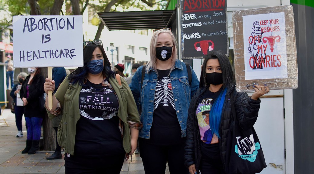 Photo depicting three female-presenting individuals holding protest signs with messages protesting against laws against abortion.