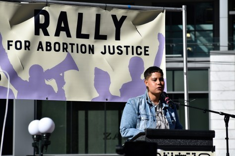 """Photo depicting Nikkita Oliver speaking into a microphone at a podium, a banner reading """"Rally for Abortion Justice"""" hangs behind them."""