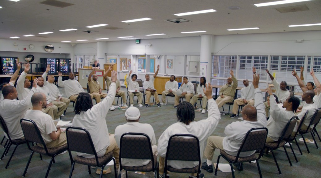 Photo depicting a group of male-presenting individuals seated in a circle wearing white prison attire. Some of the individuals have their hands raised.