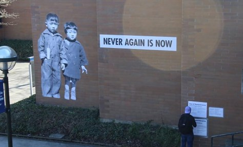 """Large image of two Japanese children, one with a tag hanging from his shirt, taken at an internment camp, pasted on a brick wall with the caption """"Never Again Is Now"""" Artwork by Erin Shigaki which was defaced by Bellevue College administration in March of 2020. (Photo: Amarra Ferrell)"""
