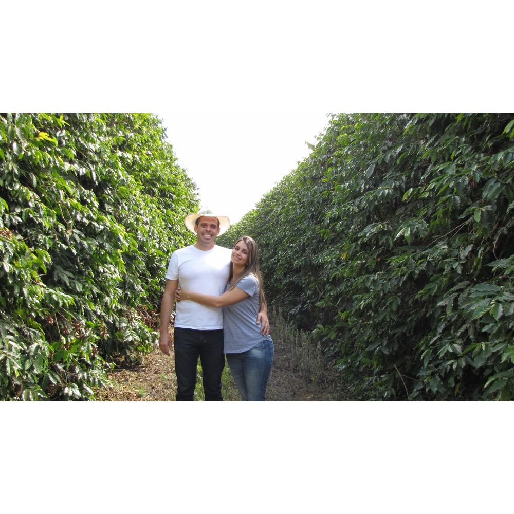 Coffee Farmers Andre Luis Garcia and Natalia Moreira standing between their coffee trees